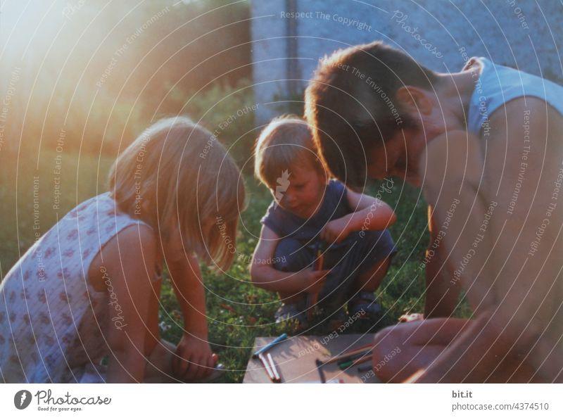 Konstruktiv l Mutter malt mit zwei Kindern im Garten im Sonnenuntergang. Mutterschaft Liebe Kindheit Lifestyle Menschen Frau Zusammensein Fröhlichkeit Glück