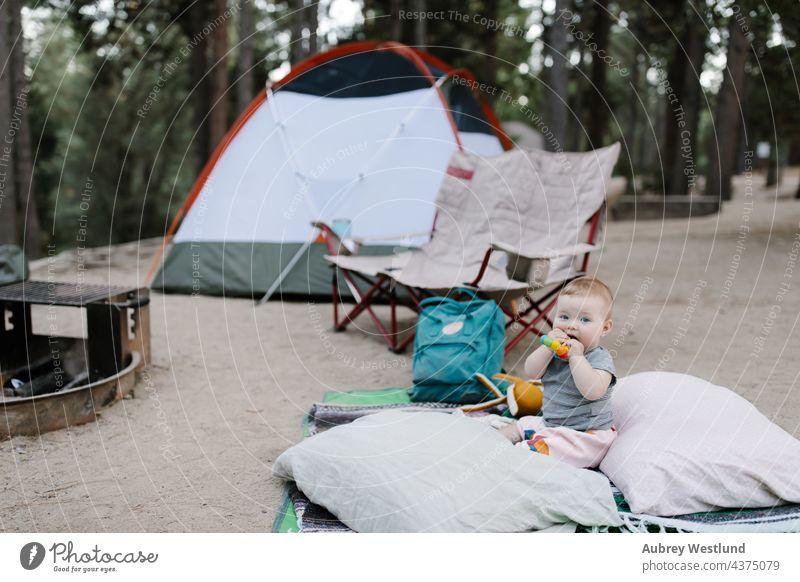 Baby spielt auf dem Boden eines Zeltplatzes 6 Monate Kalifornien Lager Wohnmobil Camping Campingplatz Stuhl Kauen Kind Kindheit Tochter Essen Familie Feuer Wald
