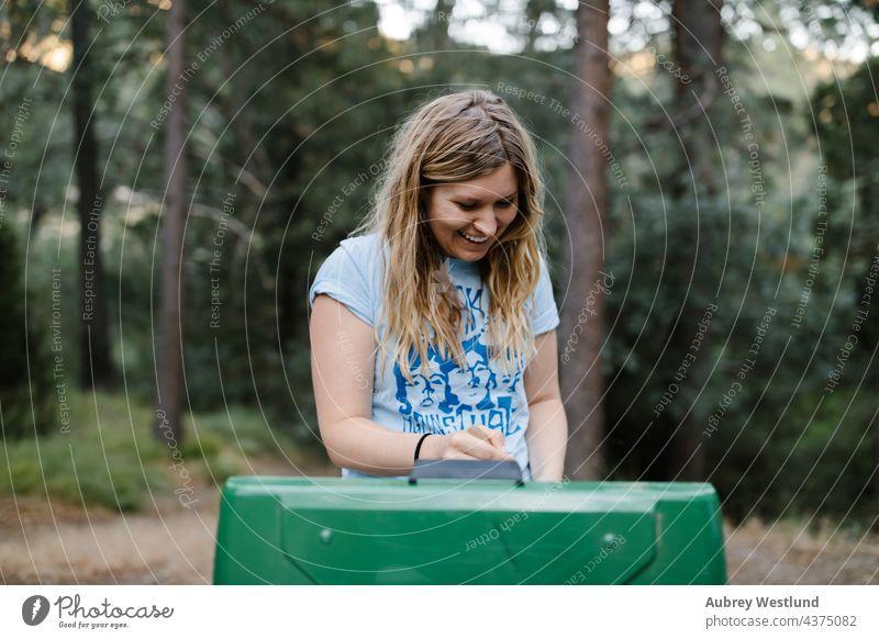 Frau kocht an einem Campingkocher im Wald Baby blond Kalifornien Lager Wohnmobil Campingplatz Kaukasier Stuhl Kind Kindheit Essen zubereiten Tochter Familie