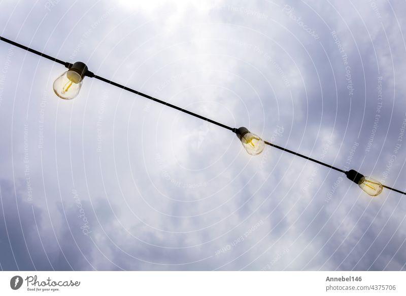 Glühende Glühbirnen hängen gegen den dunklen Abendhimmel, in einer Reihe moderne Dekoration mit Kopie Raum Licht dunkel hell Himmel Dekoration & Verzierung