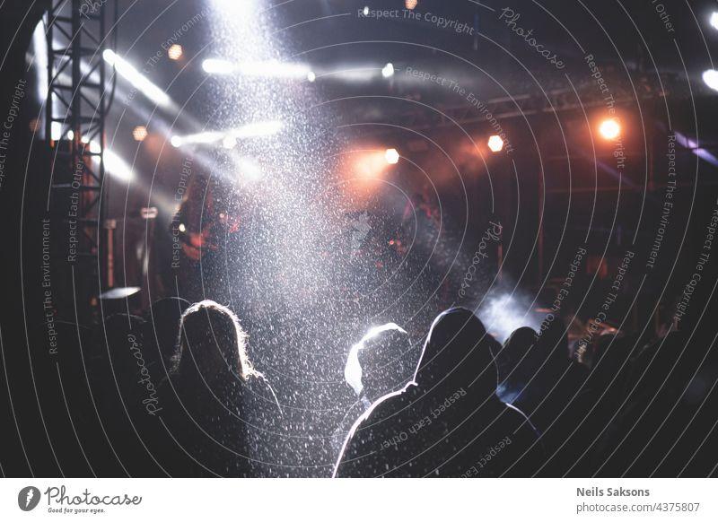 Menschen, die einem Konzert auf einem Festival lauschen, Bühnenlicht und starker Regen. Düstere Athmosphäre hinten Licht Bühnenbeleuchtung Schauplatz Musik