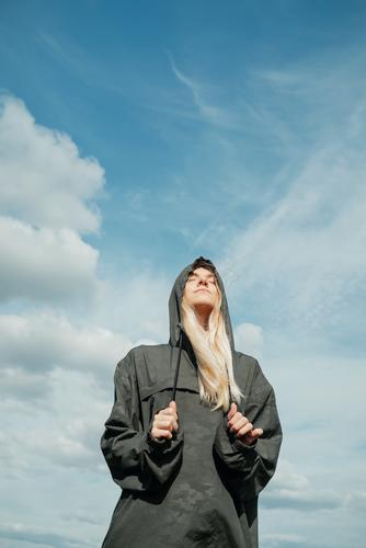 Junge blonde Frau in khakifarbenem Hemd mit Kapuze steht mit geschlossenen Augen vor dem blauen Himmel Augen geschlossen khakigrün hübsch vertikal Landschaft