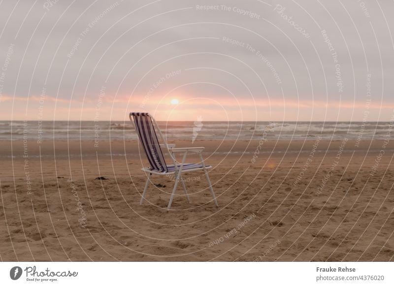 Blau-weißer Klappstuhl am Strand bei Sonnenuntergang blau gestreift Meerblick Nordsee Campingstuhl allein verlassen abends Weite Sommerurlaub Platz leer frei