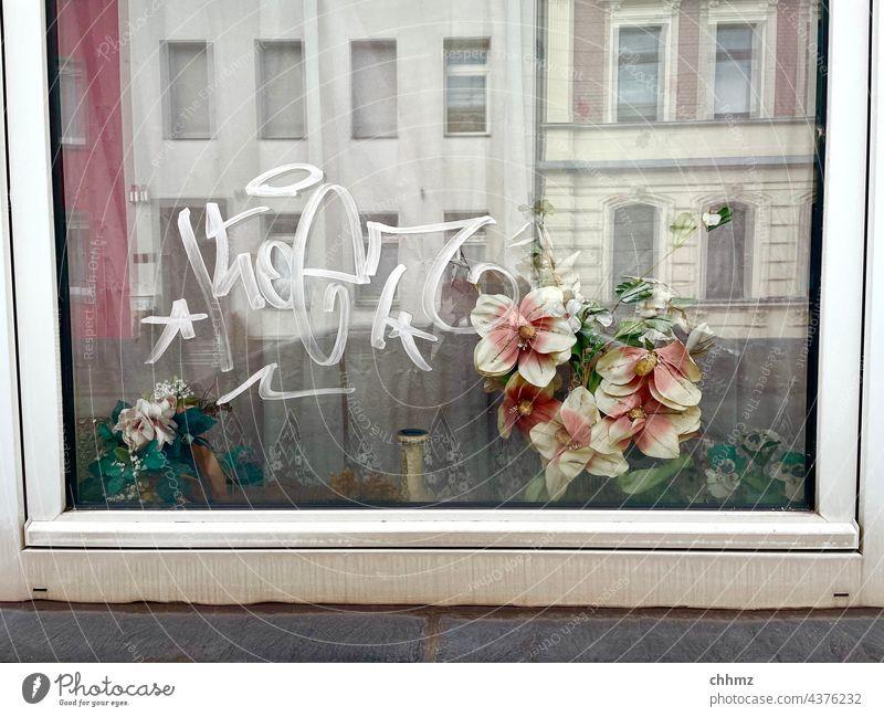 Durchblicke Fenster Glas Reflexion & Spiegelung Blumenstrauß Kunststoff Fassaden Graffiti Fensterrahmen Fensterbank verwahrlost verschmutzt alt traurig Einblick
