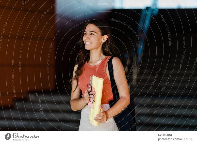 Eine lächelnde Schülerin steht auf der Treppe und hält Ordner, Brille und ein Telefon in den Händen Mädchen Freitreppe Lächeln Beteiligung Tasche jung