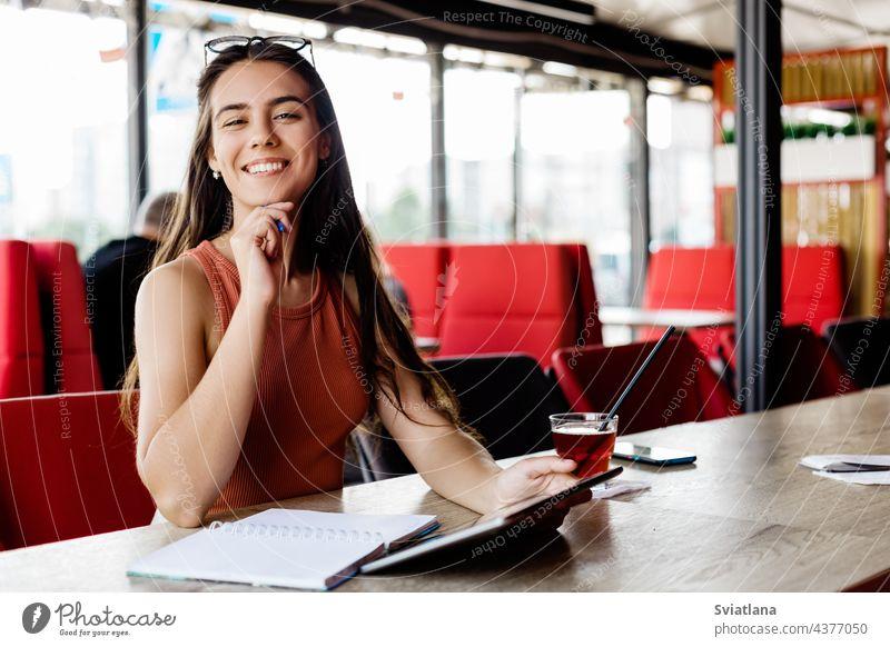 Ein schönes Mädchen mit einem Notebook und einem Tablet sitzt in einem Café und studiert oder arbeitet Notizblock Tablette Schüler Freiberufler Pause Bildung