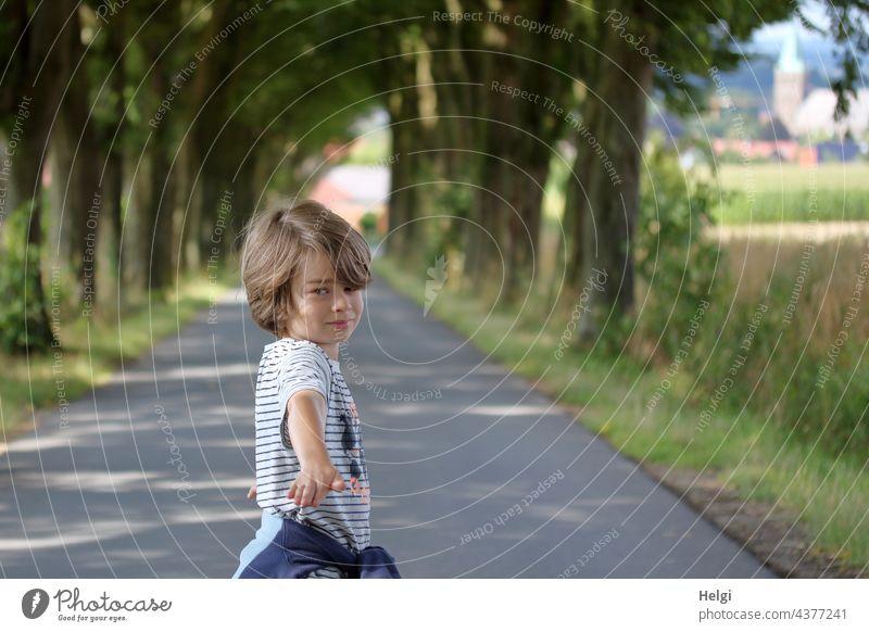 Junge steht auf einer Alleestraße, blickt und zeigt zum Fotografen Mensch Kind Kindheit Straße Baum Spaziergang draußen unterwegs Außenaufnahme Wege & Pfade