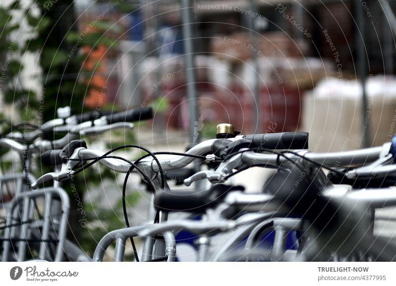 Während im Hintergrund reichlich viel Baumaterial für ein großes Haus abgestellt ist, steht im Vordergrund schon mal eine Reihe Miet-Fahrräder neben einem Baum einsatzbereit