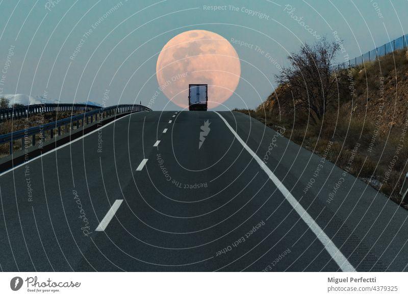 Kühltransporter auf einer Autobahn, oben auf einer Steigung mit dem Vollmond im Hintergrund. Straße Kühlwagen Lastwagen Horizont reisen Mond Verkehr Versand