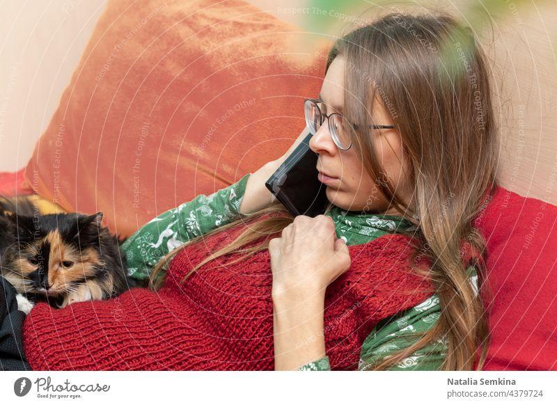 Ernste, grübelnde junge Frau, die mit ihrem Smartphone in der Hand auf der Couch sitzt und ihre Katze zu Hause hat. Junge Frau junges Mädchen sprechend