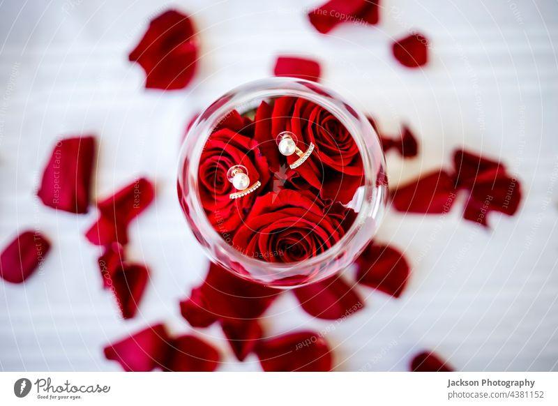 Eleganter Ohrring im Glas mit Rosen und Rosenblättern Diamanten Ohrringe Perle Blume Blütenblatt Roséwein Zubehör Glanz Glitter klein Liebe retro Glamour