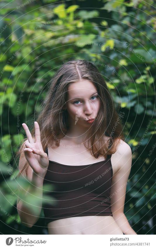 Sommerliches Porträt eines langhaarigen Teenager Mädchens, dass einen Kussmund macht und das Victory-Zeichen zeigt Vorderansicht jung blond verschmitzter Blick
