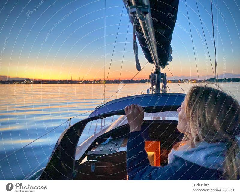 Frau auf einer Yacht schaut in Richtung Abendhimmel auf der Kieler Förde Segelboot Segeln Ostsee Meer Wasser Außenaufnahme Ferien & Urlaub & Reisen Freiheit