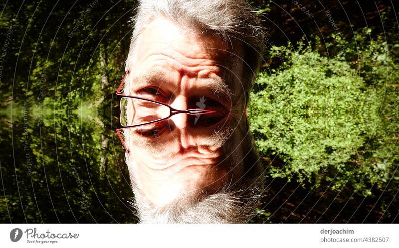 Das doppelte Männchen.  Älterer- doppelter - Mann mit Brille und vielen Falten im Gesicht, vor einer grünen Hecke. Bart Porträt freizeit Erholung rentner