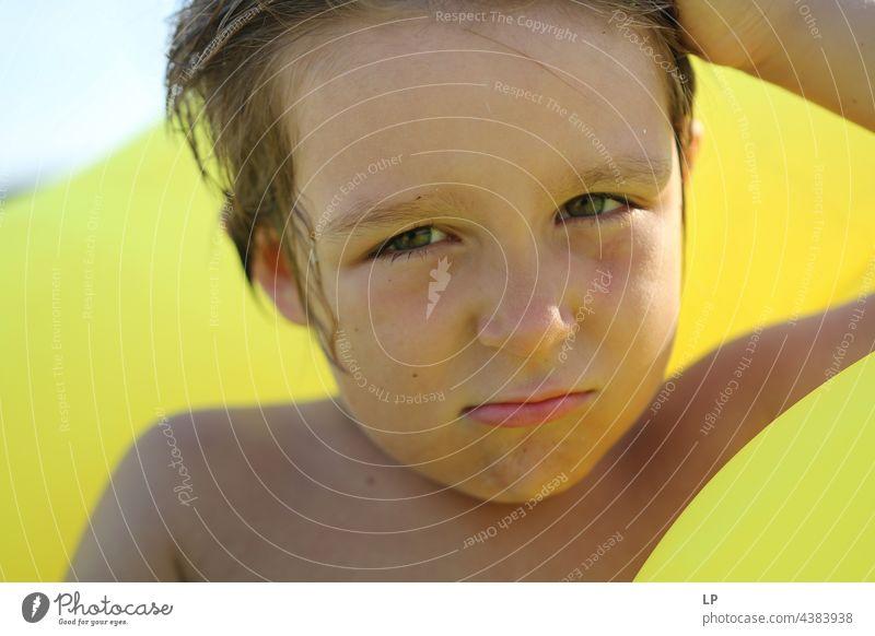 Junge am Strand auf gelbem Hintergrund mit zweifelndem Blick geheim Zufriedenheit geheimnisvoll jugendlich einzigartig Wandel & Veränderung Identität