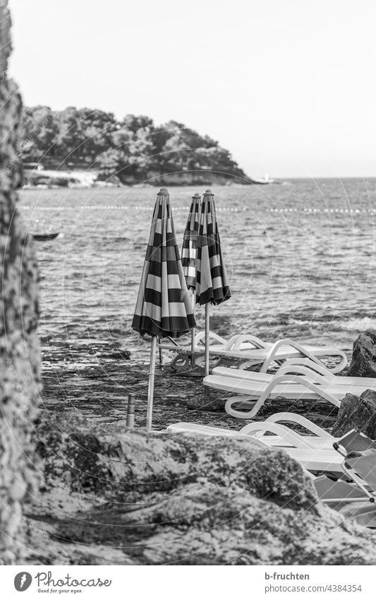 geschlossene Sonnenschirme am Strand Meer Sonnenliege Felsen Kroatien Wasser Schwarzweißfoto morgen Bucht allein Einsamkeit