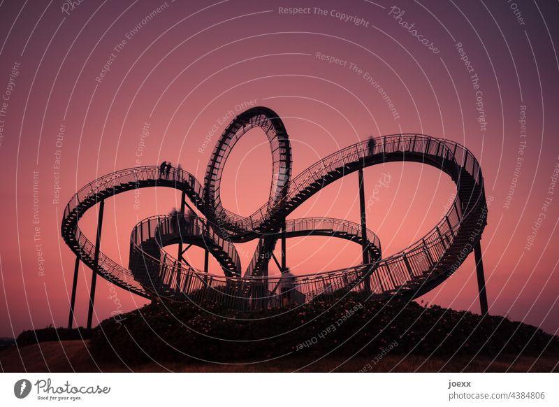 Gebogene Stahltreppe vor rotem Abendhimmel, Langzeitbelichtung Tiger and Turtle kunstwerk Treppe Metall Bogen kurvig rund Abendstimmung konstruktion