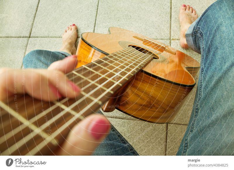 Eine Frau spielt barfuß Gitarre Musik Saite Detailaufnahme Fuß Barfuß Saiteninstrumente Musikinstrument Freizeit & Hobby Nahaufnahme Schwache Tiefenschärfe