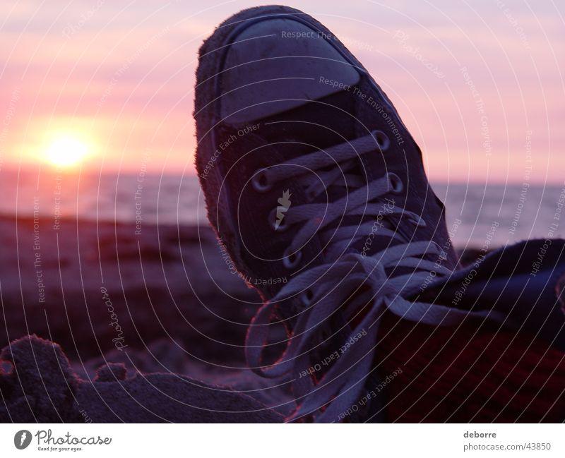 Unterhalten Sie sich mit Chuck Taylor Taylor All Stars am Strand mit der untergehenden Sonne im Hintergrund. Sonnenuntergang Schuhe Chucks Meer Wolken