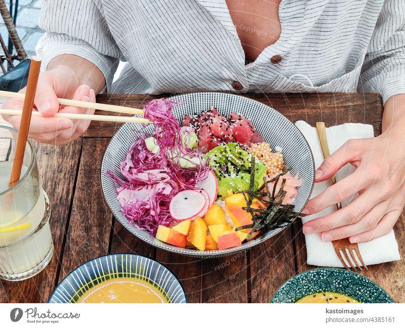 Frau essen leckere bunte gesunde natürliche organische vegetarische Hawaiian poke Schüssel mit asiatischen Stäbchen auf rustikalen Holztisch. Gesunde natürliche organische Essen Konzept