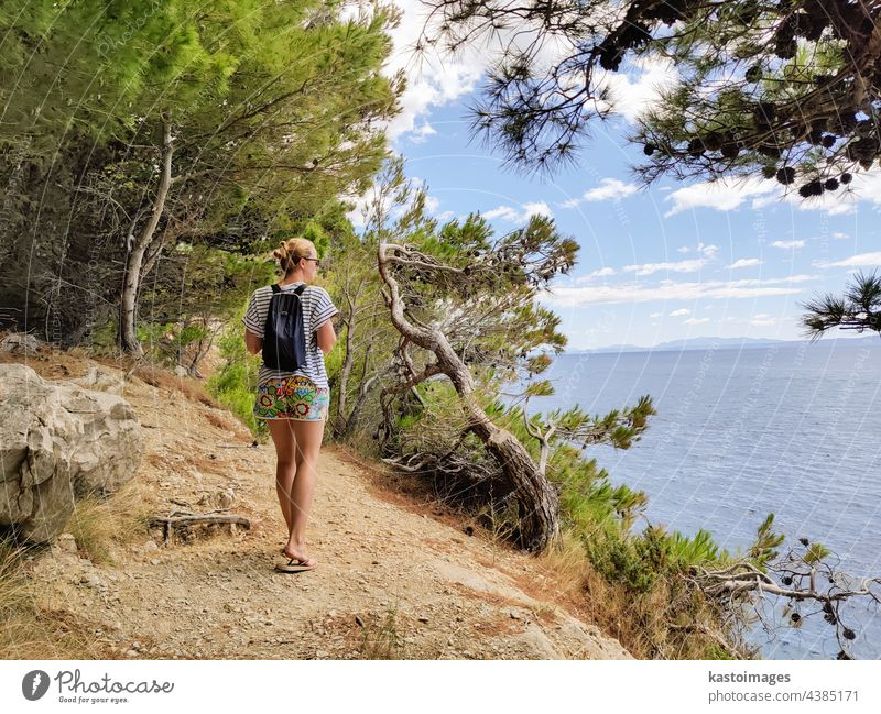 Junge aktive feamle Tourist trägt kleinen Rucksack zu Fuß auf Küstenpfad unter Pinien auf der Suche nach abgelegenen Bucht zu schwimmen allein in Frieden am Meer in Kroatien. Reisen und Abenteuer Konzept