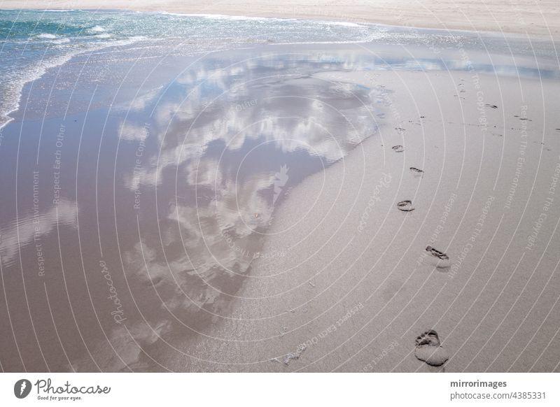 Strand nassen Sand mit frischen menschlichen nackten Fußspuren und blaue Wolke Himmel Reflexion und Wasser Wellen