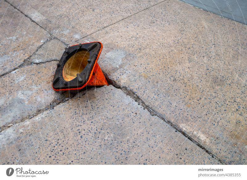 kaputter, verwitterter Bürgersteig mit Schlagloch und orangefarbenem Kegel, der verkehrt herum im Loch liegt Asphalt Hintergrund schwarz blau
