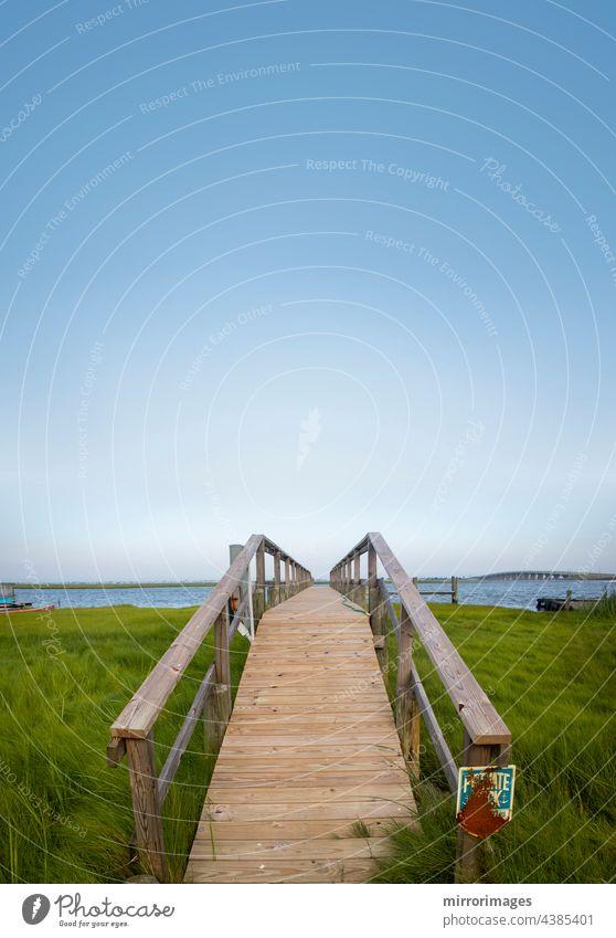 Holzsteg zum Bootssteg und zum Uferbereich Hintergrund Strand schön blau Bootsanleger und Wasserfront Brücke Gras grün Landschaft Natur schönes Tageslicht