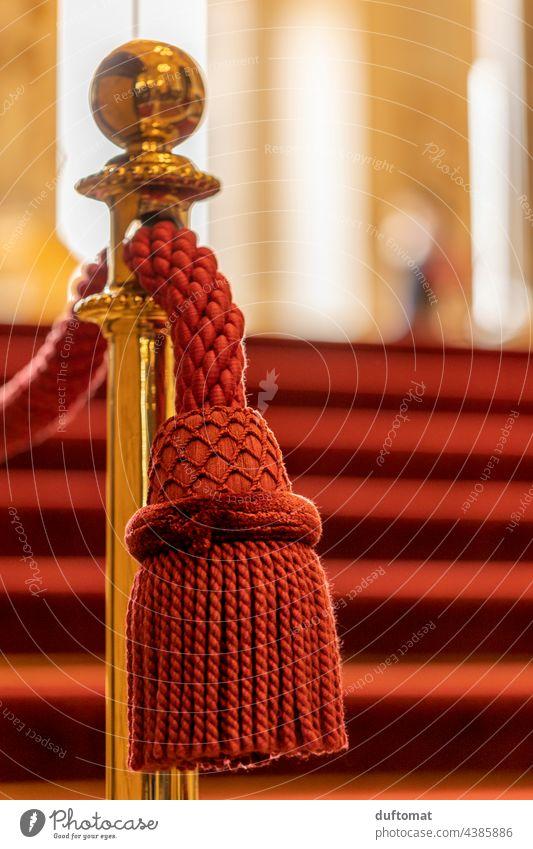Edle rote Quaste hängt an goldener Absperrung Troddel Oper Geländer edel Nahaufnahme hängen Detailaufnahme Dekoration & Verzierung Treppe abspettung Handlauf