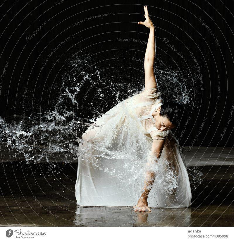 schöne Frau kaukasischen Aussehens mit schwarzen Haaren tanzt in Wassertropfen auf schwarzem Hintergrund. Die Frau trägt ein weißes Chiffonkleid beweglich aqua