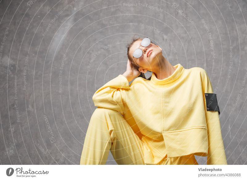 Junge Frau in gelbem Sweatshirt und Sonnenbrille auf grauem Hintergrund Porträt Model jung Mädchen Nahaufnahme Atelier Behaarung Gesicht Schönheit sinnlich