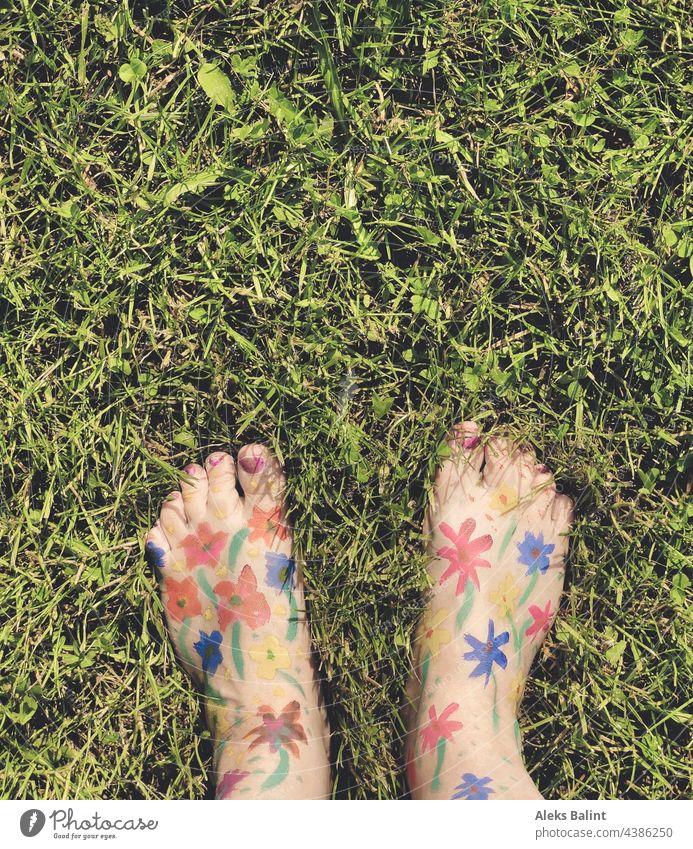 Mit Blumen bemalte Füße auf gemähter Wiese Blumenmalerei Blumenauffüßen Barfuß Sommer Außenaufnahme Rasen Natur Garten Freude Spaß haben Fröhlichkeit Bunt