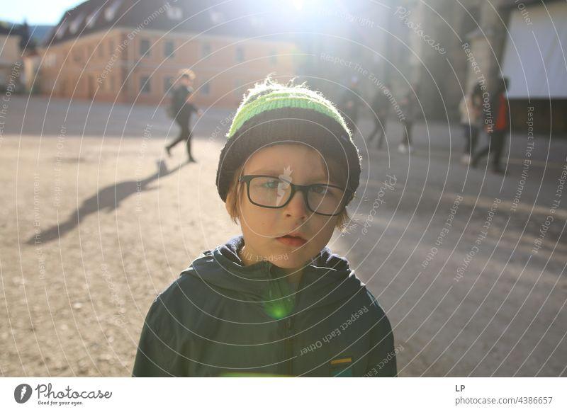 Junge mit Hut und Brille und zweifelndem Blick geheim Zufriedenheit geheimnisvoll jugendlich einzigartig Wandel & Veränderung Identität Sinnestäuschung
