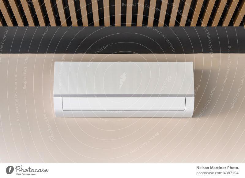 Weißes Klimagerät auf beiger Wand Kühler cool kalt kühlen erwärmen belüftet Temperatur Ventilator Wind Industrie Gerät vereinzelt elektronisch wandmontiert