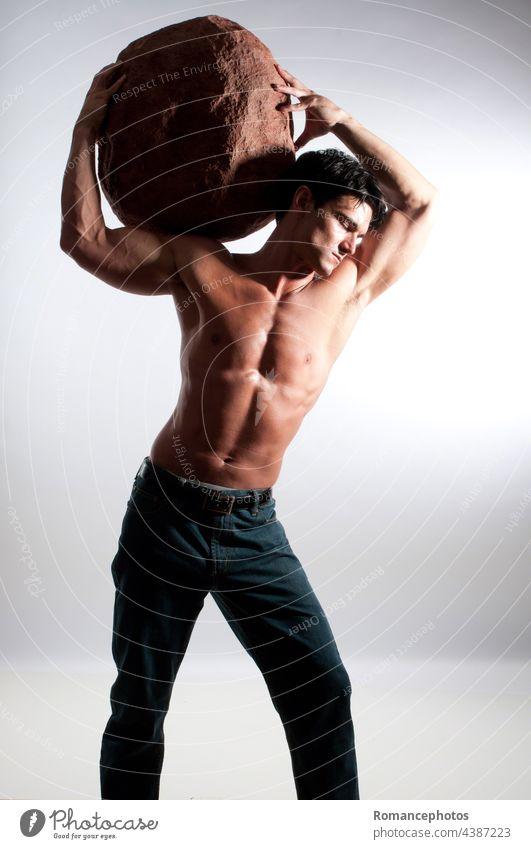 Der sexy Mann hält einen riesigen Stein. gutaussehend zäh männlich Coolness attraktiv Gesicht Lifestyle whimiscal paranormal Hintergrund Blick statuesk