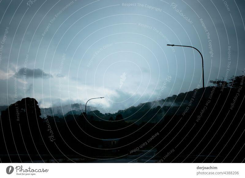 Die Sonne scheint noch etwas. Eine Nebelwand kriecht durch das Tal. Zwei große Laternen stehen bereit um bei der einsetzenden Dunkelheit zu brennen.  Im  Vordere Teil des Bildes ist es schon dunkel.