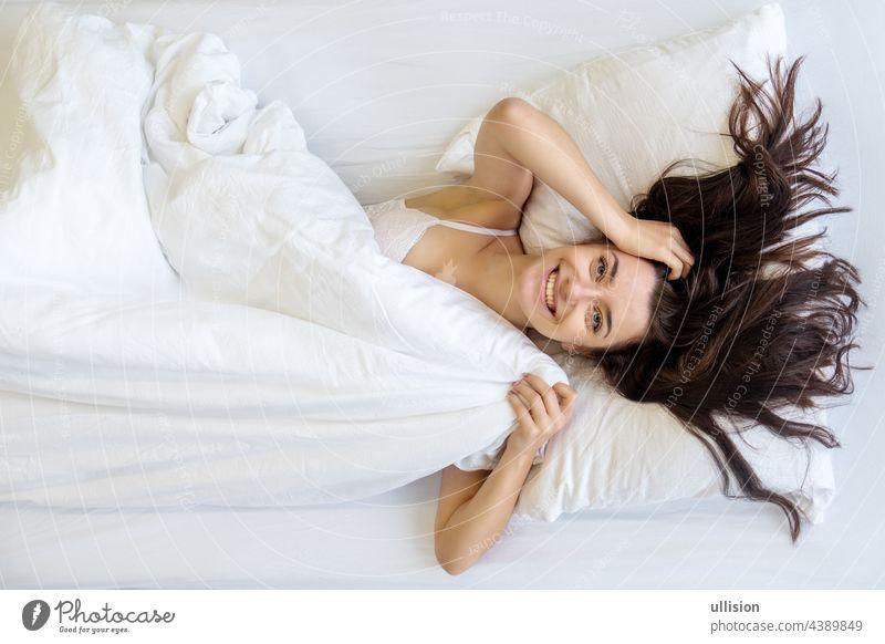 Blick von oben auf eine attraktive, junge, sexy, dunkelbraunhaarige Frau, lächelnd, lachend, das frische, weiche Bett genießend, am Morgen, Kopie Raum. Lächeln