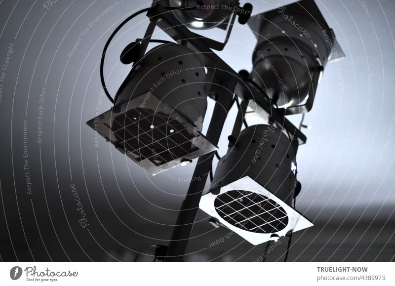 Studioleuchte mit vier Scheinwerfern aus Aluminium, die jeweils mit einem Schutzgitter versehen an einen Querträger in alle Richtungen dreh- und schwenkbar montiert sind, schräg monochrom fotografiert