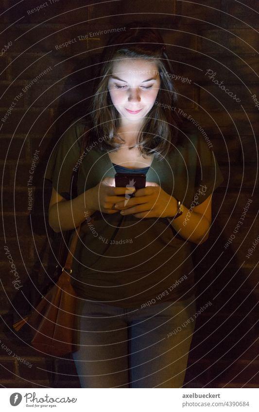 junge Frau benutzt Handy im Dunkeln benutzend Smartphone Licht Lichtschein Beleuchtung leuchten Technik & Technologie Lifestyle Telefon Internet Texten