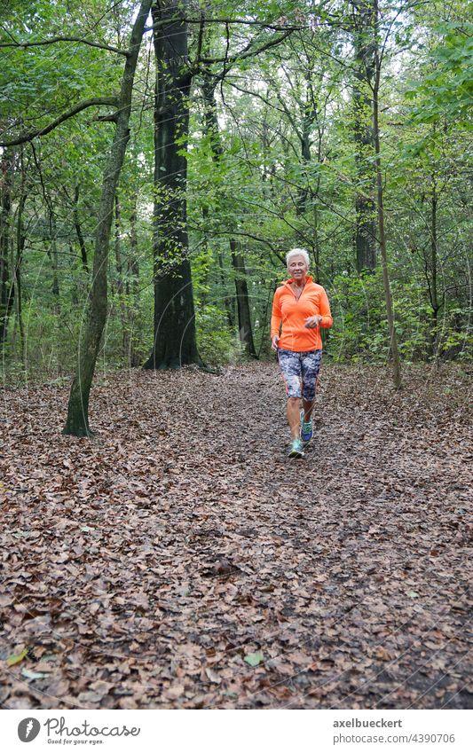 Seniorin in Sportbekleidung joggt durch den Wald seniorin Joggen Jogger Jogging laufen aktiv Fitness Gesundheit sportlich Lifestyle im Freien Frau Training