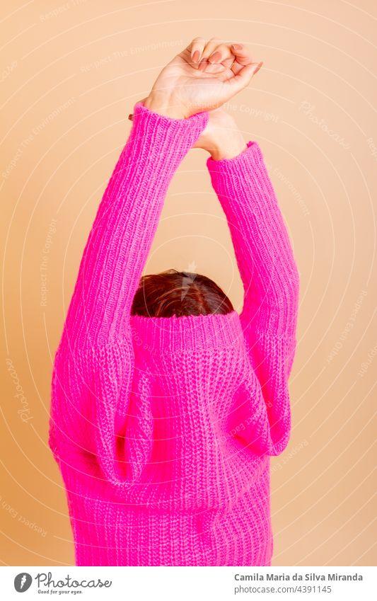 Porträt eines Mädchens, das sich einen schicken Pullover über den Kopf zieht. Frau mit gebundenem Haar, kalt, versteckt sich unter ihrem Pullover. Mode-Shooting.