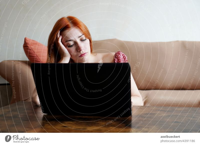 traurig einsam deprimiert bei der Arbeit von zu Hause aus am Laptop Homeoffice gelangweilt Wohnzimmer Frau Heimarbeitsplatz echte Menschen Computer überarbeitet