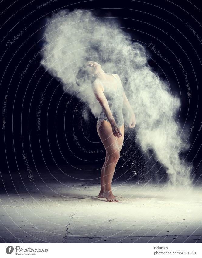 schöne kaukasische Frau im schwarzen Bodysuit mit sportlicher Figur tanzt in einer weißen Mehlwolke auf schwarzem Hintergrund Aktion aktiv Erwachsener Kunst