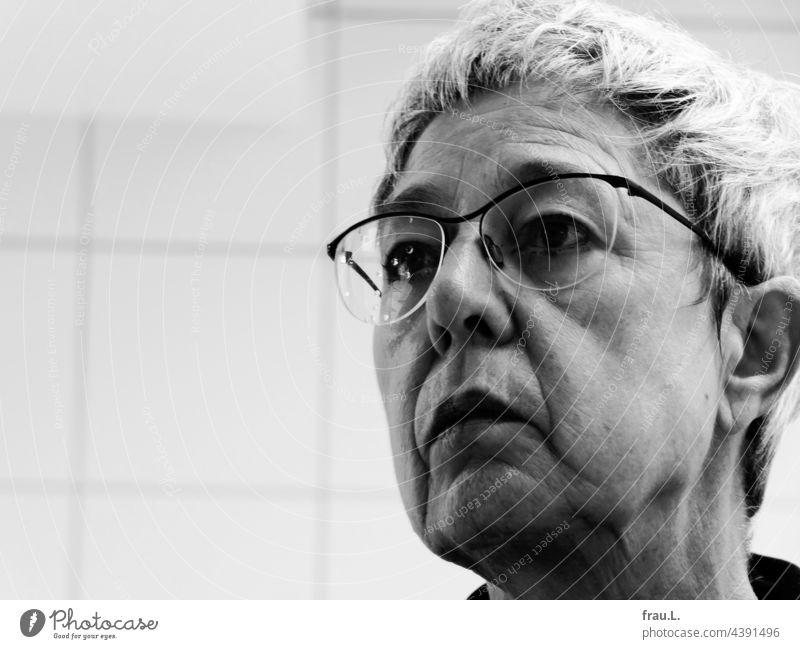 Alte Frau mit Wassertropfen auf der Brille Porträt Gesicht Kacheln Fliesen graue Haare erstaunt genervt Falten androgyn Gesichtsausdruck Kopf