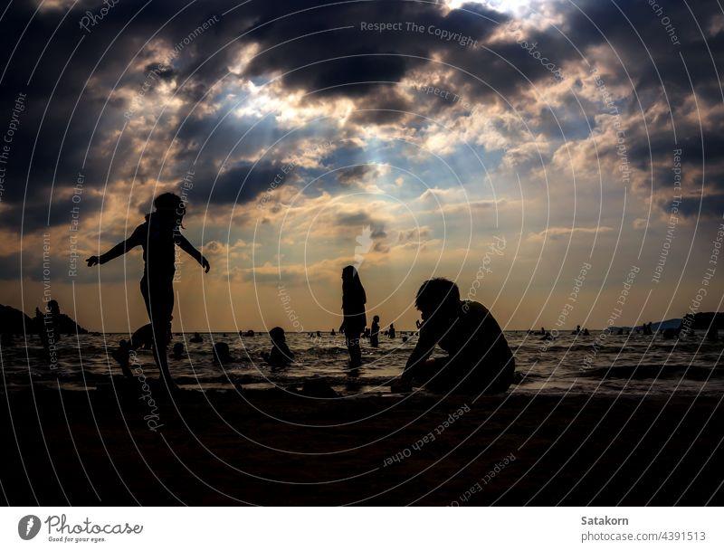 Silhouetten von Menschen spielen im Meer an einem öffentlichen Strand Landschaft Himmel Sand Abend Urlaub MEER Sonne Sonnenuntergang Sommer jung Wasser Natur