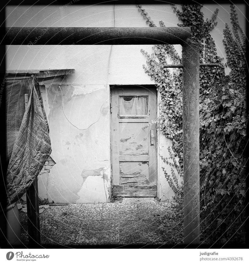 Eingang Tür Haus Gebäude Wand Architektur Mauer verlassen leerstehend teppichstange Plane Quadrat alt trist Eingangstür grau wohnen Wohnhaus