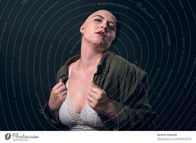 Porträt einer jungen Frau mit Männerhemd, Mütze und Bustier Atelier selbstbewusst Herz Liebe Leidenschaft Hemd Finger ernst stark Kraft kampfstark kurz