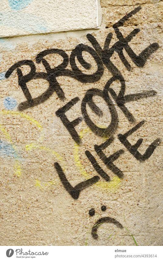 BROKE FOR LIFE steht in schwarzen Großbuchstaben an der beigefarbenen, besprayten Wand / fürs Leben pleite broke for life Graffito Graffiti Farbe Wort verputzt