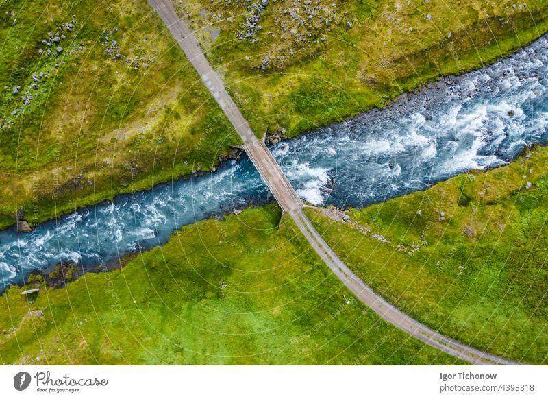Luftaufnahme von oben auf einen milchig blauen Fluss und eine Brücke, Island Antenne abgelegen Felsen Landschaft Draufsicht Park Tourismus reisen Baum