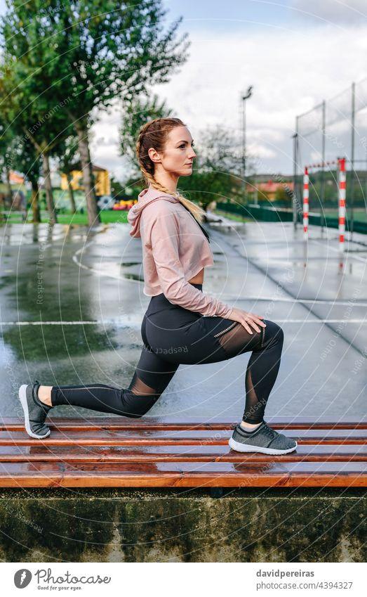 Junge Sportlerin streckt die Beine im Freien strecken auf einer Bank Boxerflechten Frau Athlet Körper Aufwärmen Training geduckt trainiert. sportlich Sweatshirt
